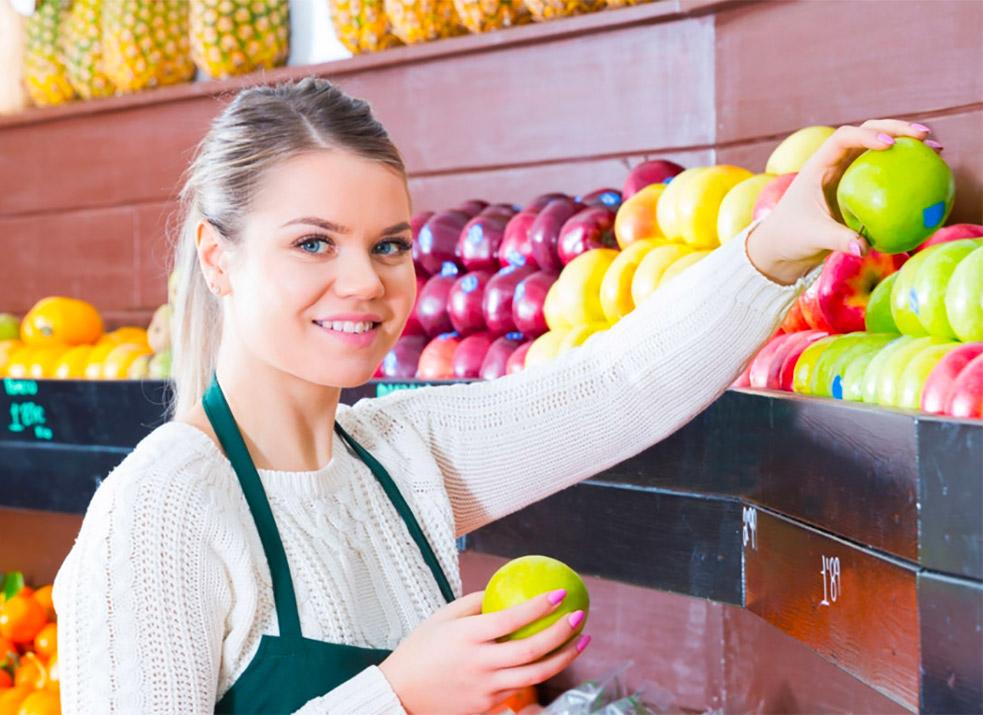 employee stocking produce shelf